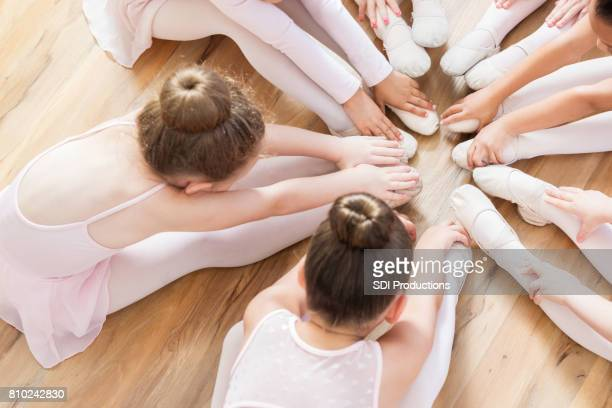 Unrecognizable ballerinas sit with their feet together while touching toes