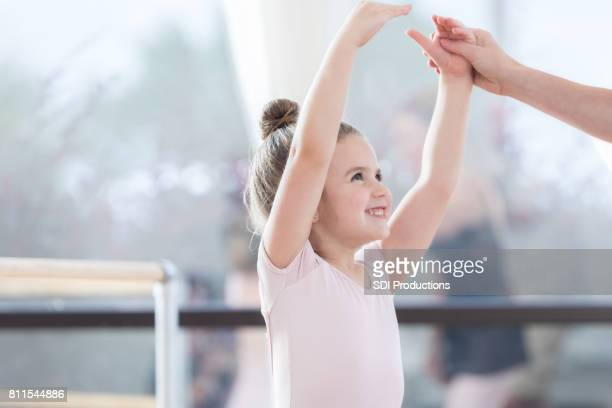 Unrecognizable ballet instructor helps young girl