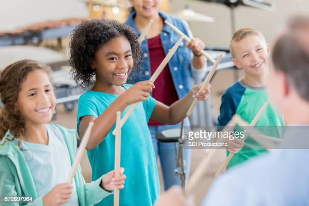 unrecognizable band teacher teaches drumming to students - percussion instrument stock photos and pictures