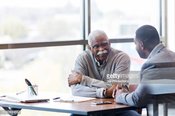 unrecognizable banker takes time to visit with senior customer - businesswear stock pictures, royalty-free photos & images