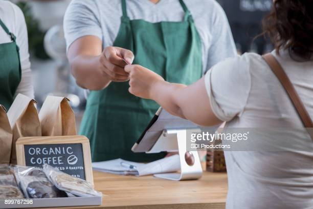 Unrecognizable barista accepts payment at counter
