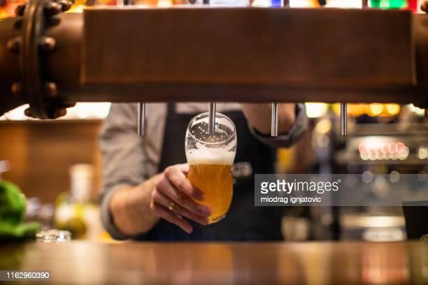 パブでビールを注ぐ認識できないバリスタ - ビールサーバー ストックフォトと画像