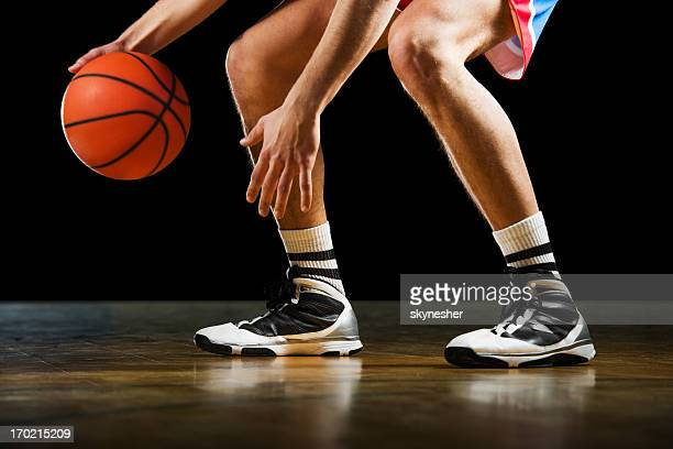 Unrecognizable basketball player dribbling.