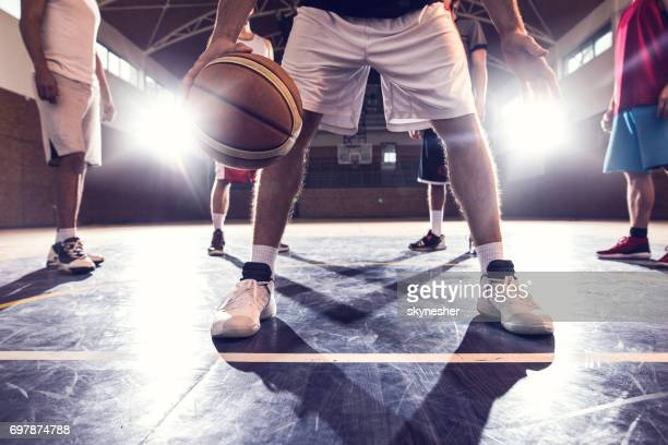 unrecognizable basketball player with a ball on basketball court with his teammates in the background. - basketball team stock pictures, royalty-free photos & images