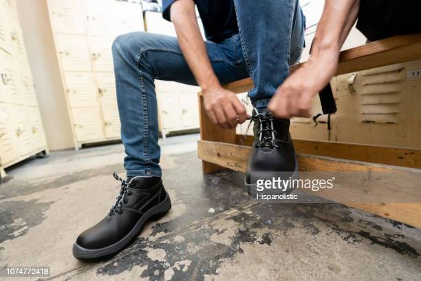 unrecognizable blue collar worker putting on working boots at the locker room in a factory - work shoe stock photos and pictures