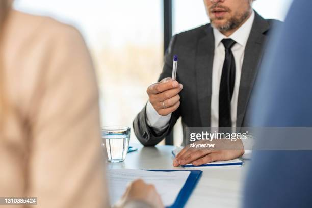 unrecognizable businessman holding a pen while talking in the office. - mortgage stock pictures, royalty-free photos & images