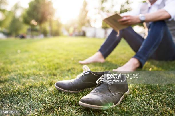 Unrecognizable businessman in the city park sitting on grass reading book