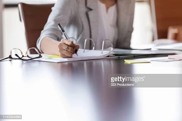 unerkennbare geschäftsfrau arbeitet am tisch - weibliche angestellte stock-fotos und bilder