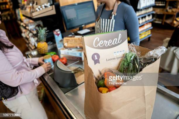 unrecognizable cashier scanning products before packing them up for female customer - grocery bag stock pictures, royalty-free photos & images
