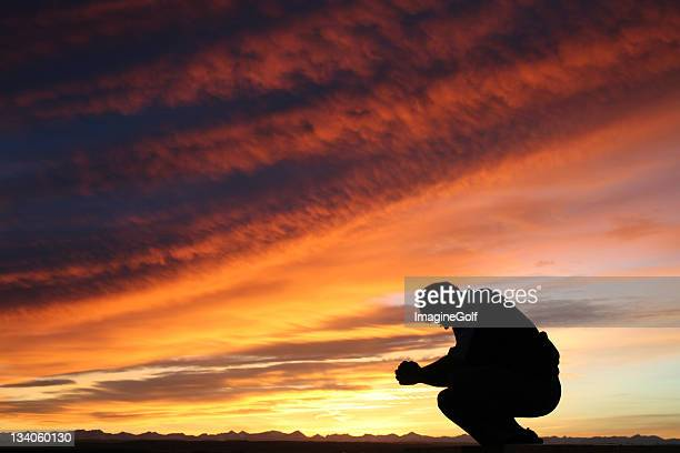 Unrecognizable Caucasian Male Praying Against Dramatic Sunset Sky