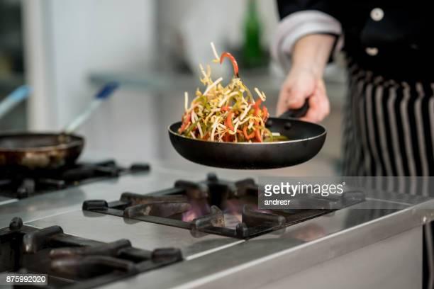 Unrecognizable chef sautéing vegetables at a restaurant