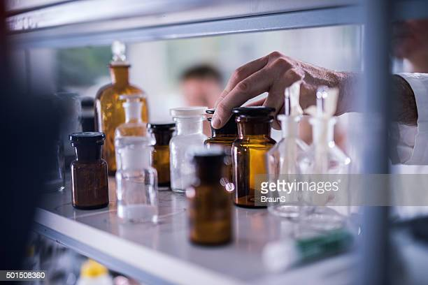 Unrecognizable chemist choosing the right bottle for his experiment.