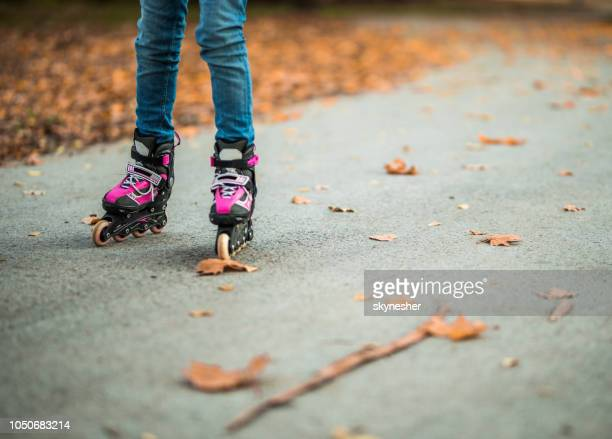 unrecognizable child roller skating in autumn day. - inline skate stock photos and pictures