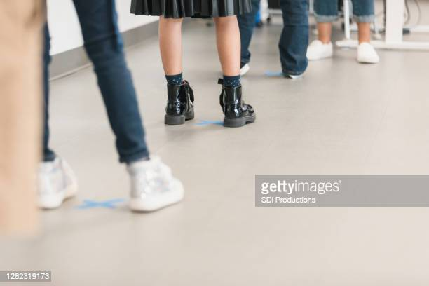 unrecognizable children social distance while standing in line - childhood stock pictures, royalty-free photos & images