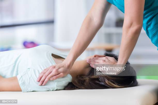 unrecognizable chiropractor adjusts woman's neck - human head stock pictures, royalty-free photos & images