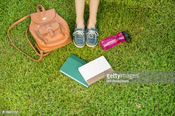 Unrecognizable college student sits in grass on campus