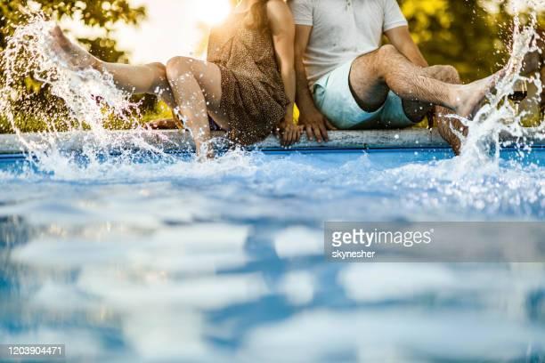 unrecognizable couple having fun while splashing water in the pool. - gamba umana foto e immagini stock