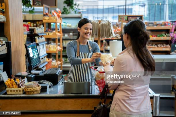 unrecognizable customer at supermarket handing products to friendly cashier for checkout - cash register stock pictures, royalty-free photos & images