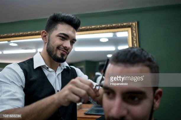 unrecognizable customer getting a hair cut at a barber shop - hispanolistic stock photos and pictures