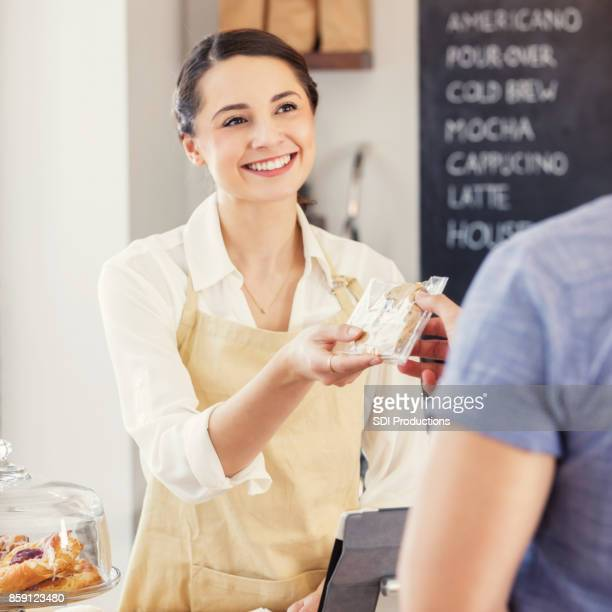 Unrecognizable customer purchases a cookie at a cafe