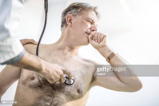 nicht erkennbare arzt untersuchen senior mannes brust. - raucher lunge stock-fotos und bilder