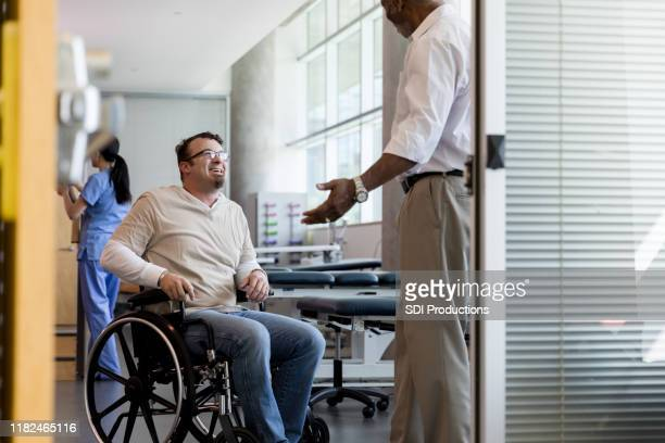 unrecognizable doctor stops by therapy room to congratulate patient - outpatient care stock pictures, royalty-free photos & images