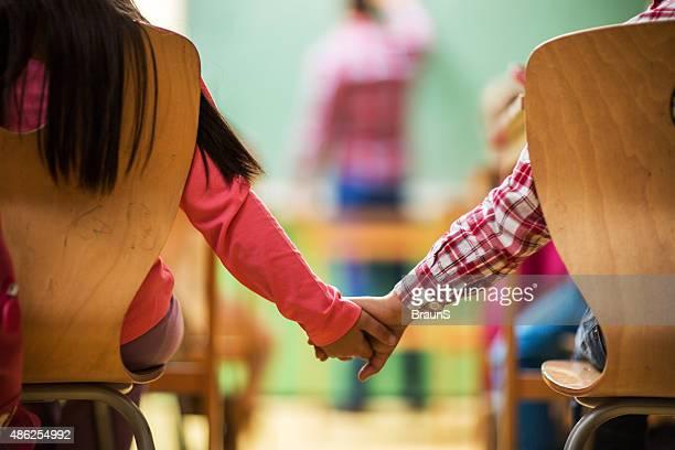 Unrecognizable elementary school children holding hands in the classroom.