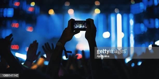 onherkenbaar fan filmen concert met een smartphone. - live evenement stockfoto's en -beelden