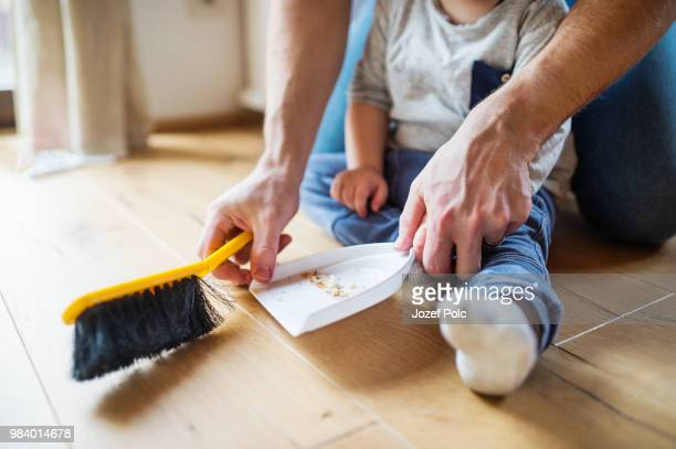 unrecognizable father and toddler with brush and dustpan. - dustpan and brush stock pictures, royalty-free photos & images