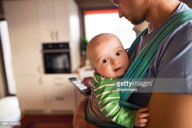 Unrecognizable father at home in the kitchen holding smart phone, texting, baby son in sling