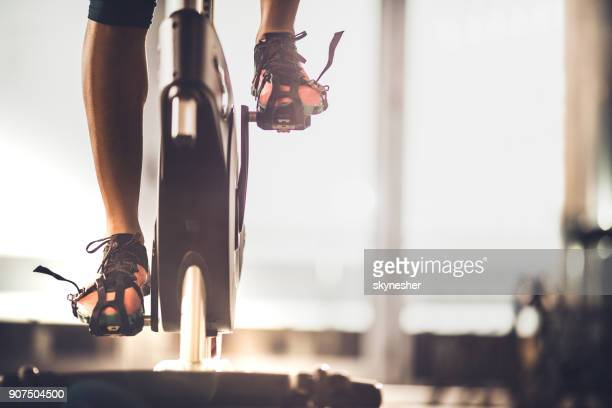 unrecognizable female athlete exercising on exercise bike in a gym. - gym stock pictures, royalty-free photos & images