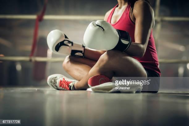 認識できない女性のボクサーはボクシングのリングでヨガの練習します。