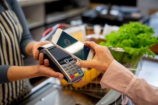 Unrecognizable female customer paying for groceries with smartphone 1128048513