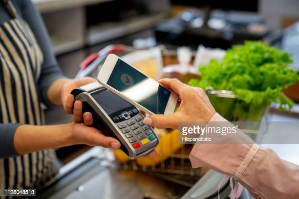 unrecognizable female customer paying for groceries with smartphone - cash register stock pictures, royalty-free photos & images