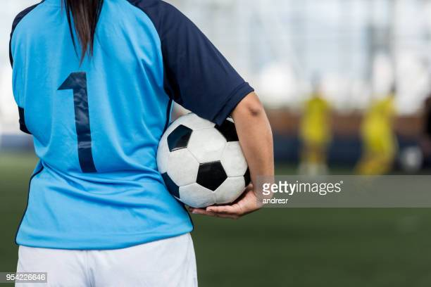 unrecognizable female soccer player showing the back of her shirt and holding the soccer ball - sports jersey stock pictures, royalty-free photos & images