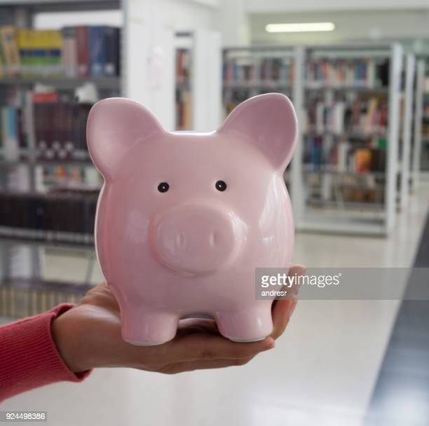 Unrecognizable female student holding a piggy bank at a college library