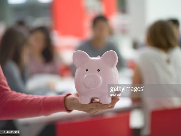Unrecognizable female student holding a piggy bank - Student loans
