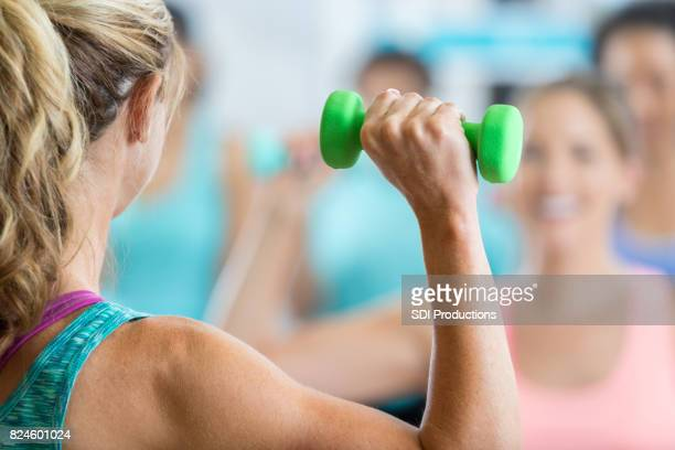 Unrecognizable fitness instructor leads weight training class