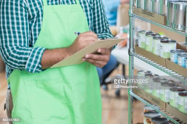 Unrecognizable food bank volunteer works in store room