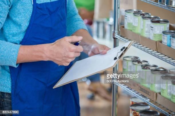 Unrecognizable food bank volunteer works on inventory