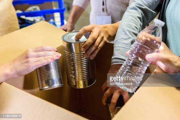 unrecognizable food bank volunteers organized donated items - humanitarian aid stock pictures, royalty-free photos & images