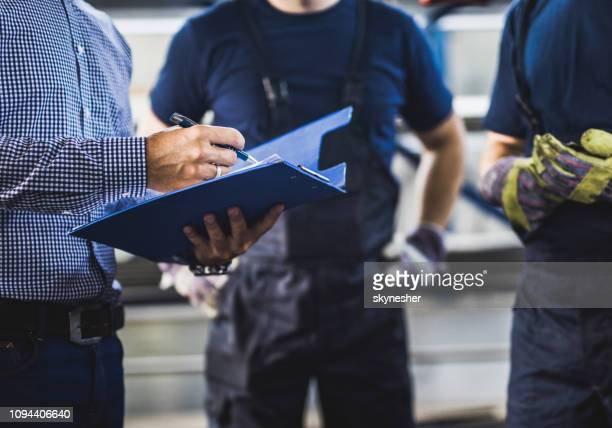unrecognizable foreman going through paperwork with manual workers in a warehouse. - construction industry stock pictures, royalty-free photos & images
