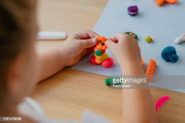 可塑性で遊ぶ認識できない女の子 - 粘土 ストックフォトと画像