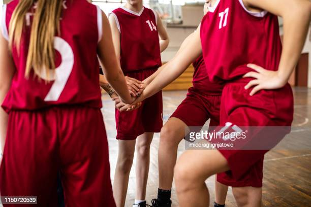 unrecognizable girls stacking hands in school gym - team sport stock pictures, royalty-free photos & images