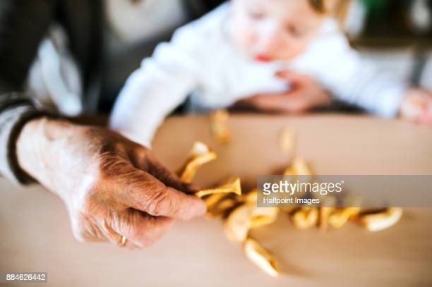 Unrecognizable grandmother with grandson at home storing dried apples.