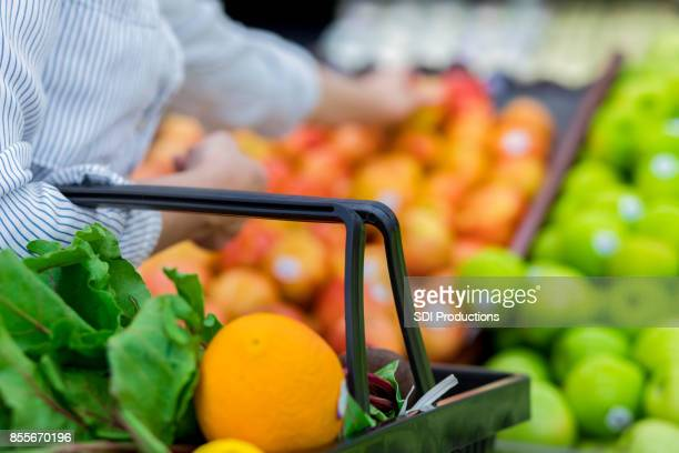 Unrecognizable grocery store customer reaches for fresh produce