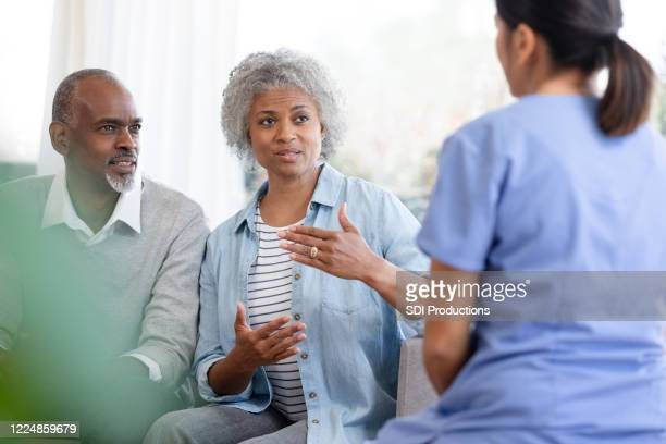 unrecognizable homehealth nurse listens to senior couple - african american man helping elderly stock pictures, royalty-free photos & images