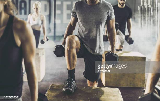 unrecognizable male athlete having cross training with dumbbells in a gym. - cross training stock pictures, royalty-free photos & images