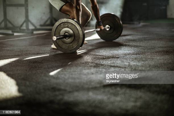 unrecognizable male athlete having weight training with barbell in a gym. - athleticism stock pictures, royalty-free photos & images