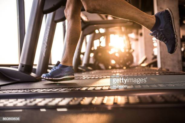 Unrecognizable male athlete running on treadmill in health club.